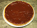 Warm the ganache until its melted and liquid, then spread it quickly over the top of the tart