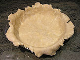 Leave the dough that overhangs the lip of the pie plate in place and refrigerate until needed