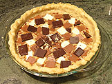 Placed each type of the chocolate pieces on top of the pie, one at a time to ensure they are evenly distributed